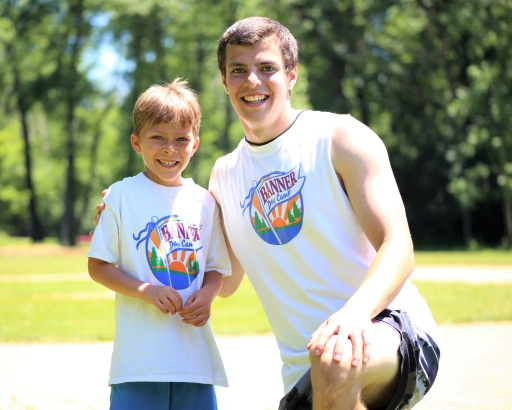 Young camper smiling with a counselor
