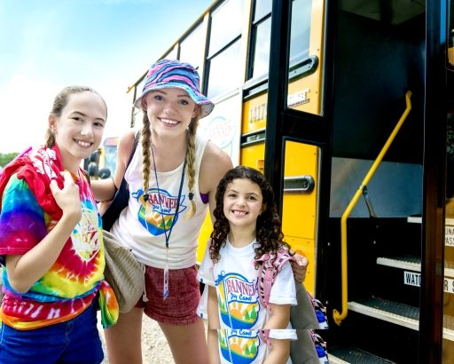 Two campers getting off the bus smiling with a CIT camper