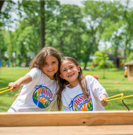 Two girl campers smiling together at the sling shot station