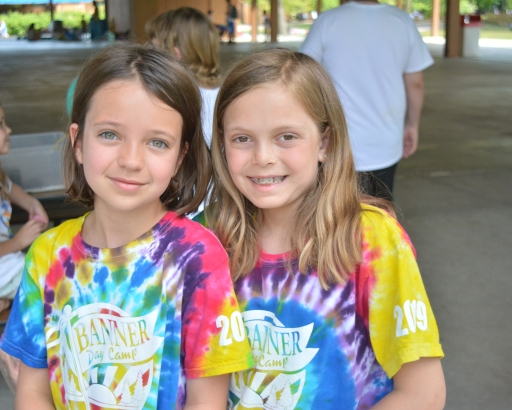 Two campers smiling together in banner day camp shirts