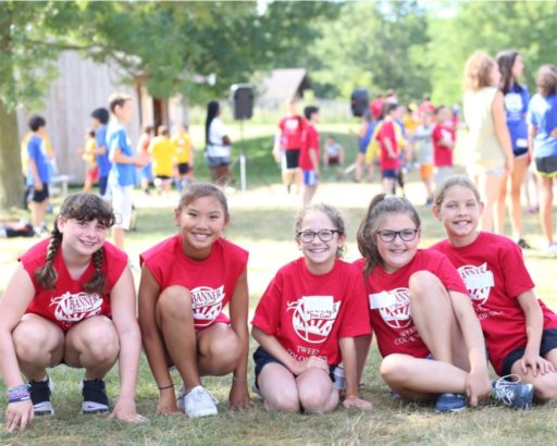 Group of girl campers all in banner day camp shirts smiling on the grass together