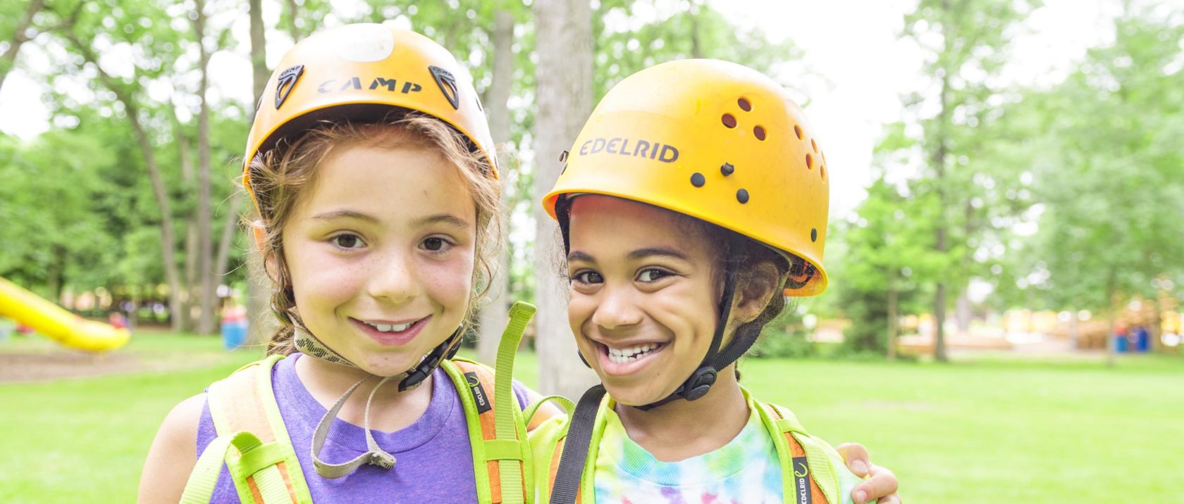 Two girl campers with zipline gear on smiling together