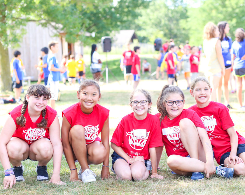 Group of girl campers sitting on grass together in matching red shirts