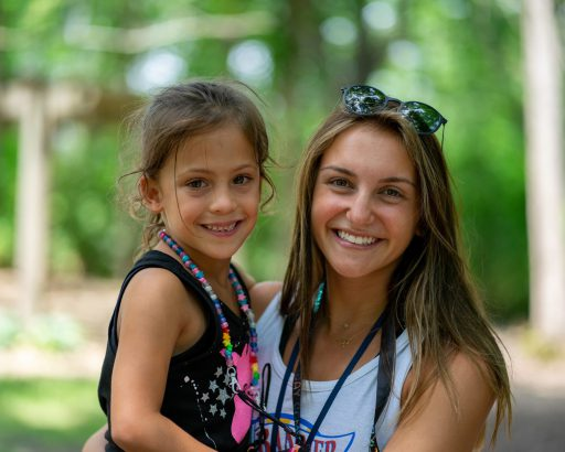 Female counselor holding a girl camper and smiling