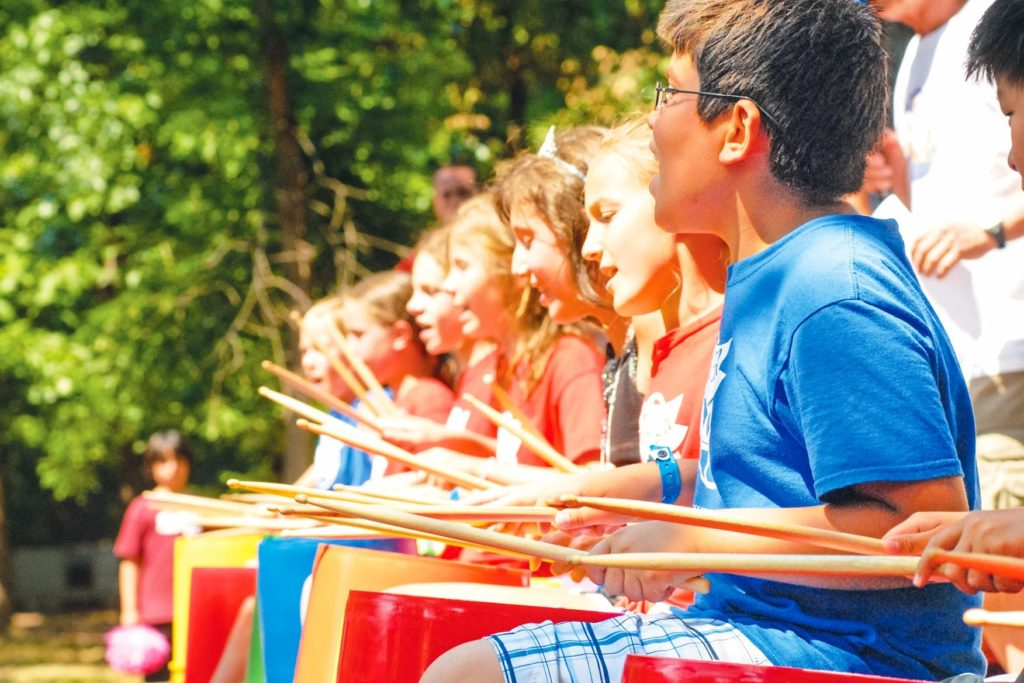 A row of campers playing the drums