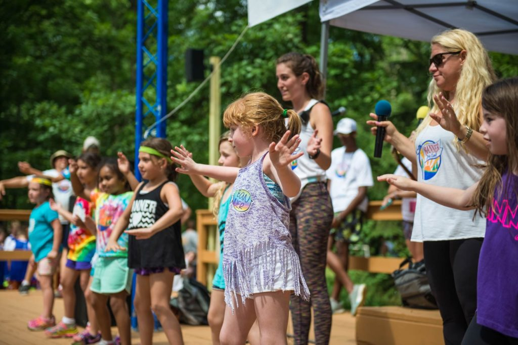 Young campers performing a dance at the ampitheater