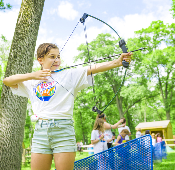 Girl camper with bow and arrow ready to shoot an archery target