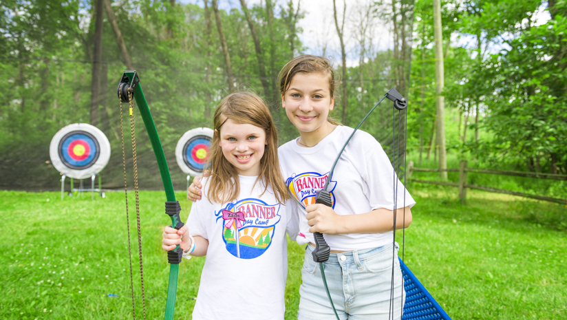 Two girl campers with bows and arrows smiling by the archery field