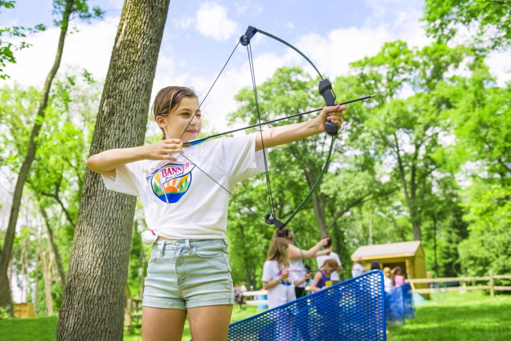 A camper aims and prepares to shoot an arrow