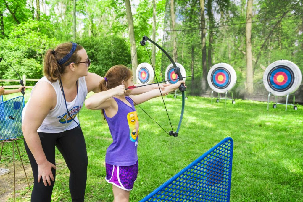 A counselor helping a camper aim and shoot an arrow