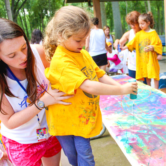 Girl camper doing arts and crafts with the help of a staff member