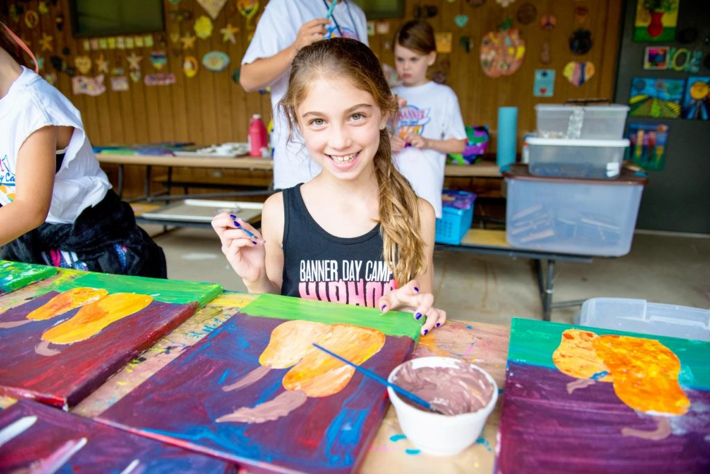 A girl smiles as she paints fruit