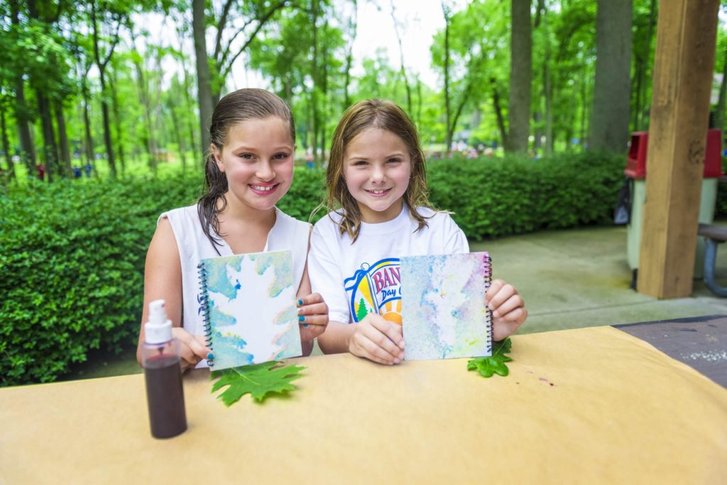 Two campers hold up their leaf rubbings