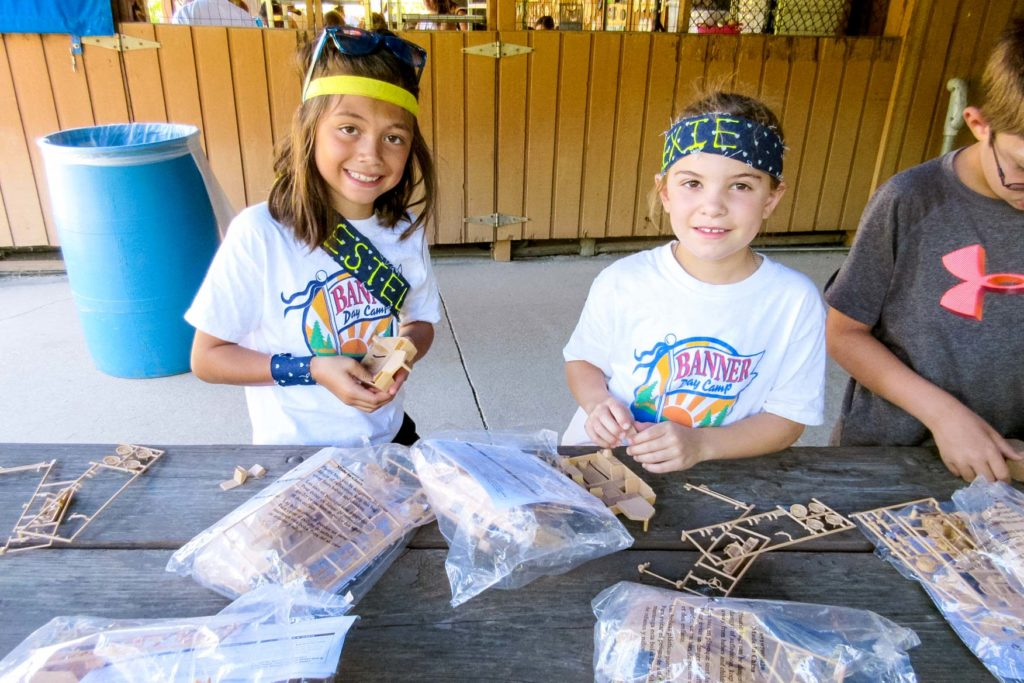 Two campers get pieces together for building something