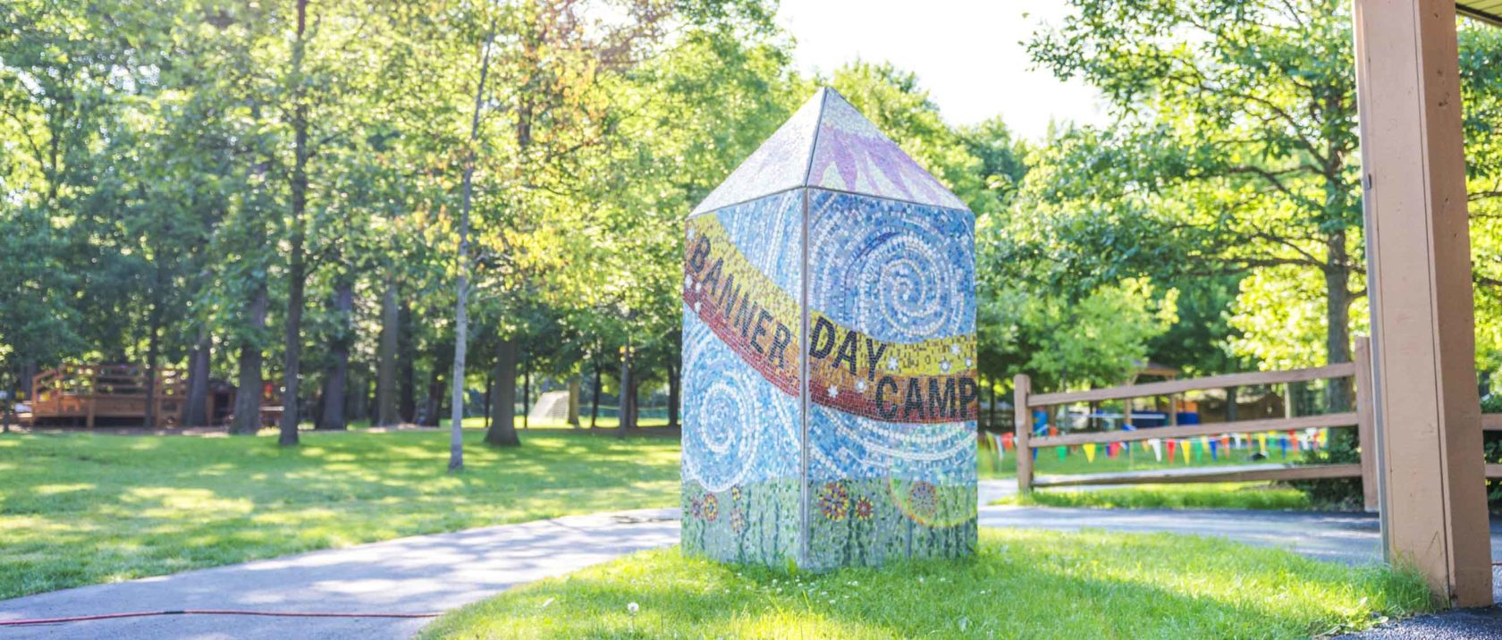 Banner Day Camp mosaic on a pillar in a field