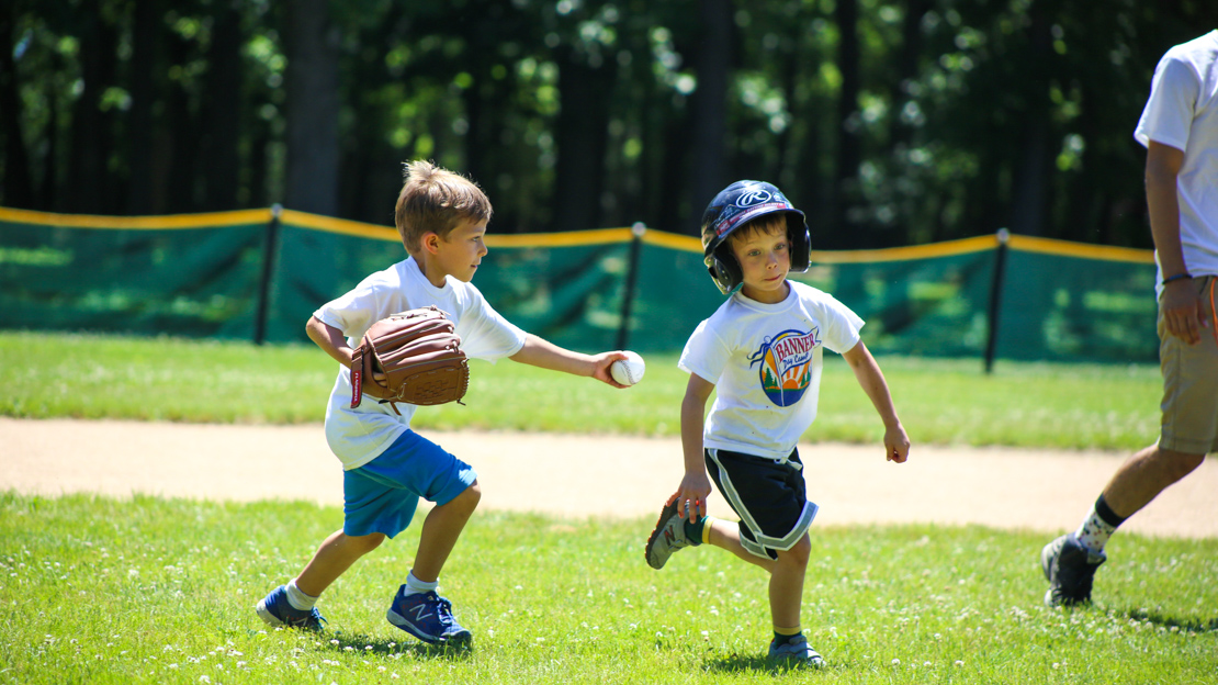 Boy camper about to tag a runner in baseball