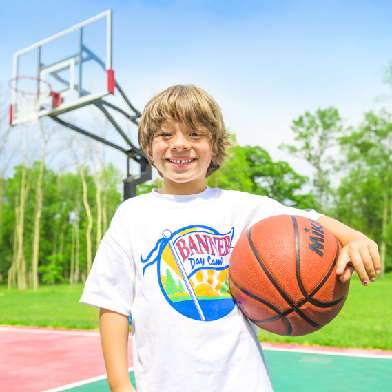 Boy camper holding a basketball and smiling