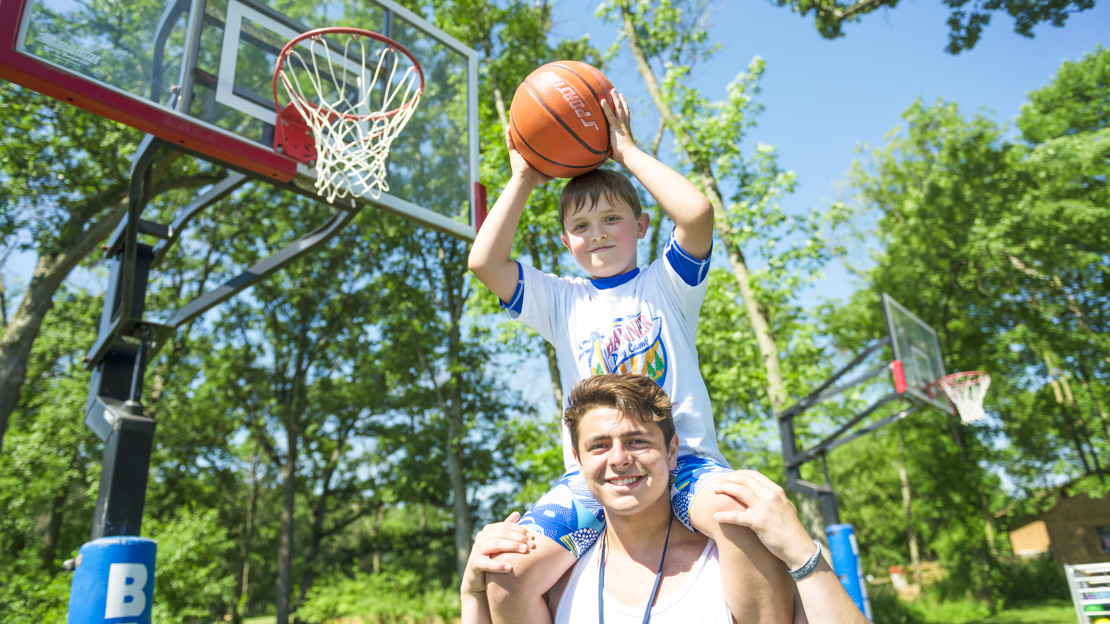 Boy camper holding a basketball up to the hoop while sitting on male staff members shoulders