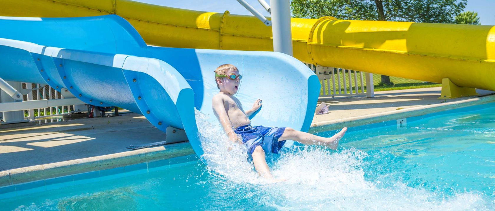 Boy camper sliding down water slide
