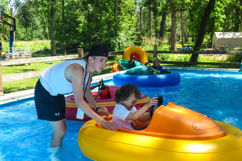 A counselor pushes a young camper along in an orange and yellow bumper boat