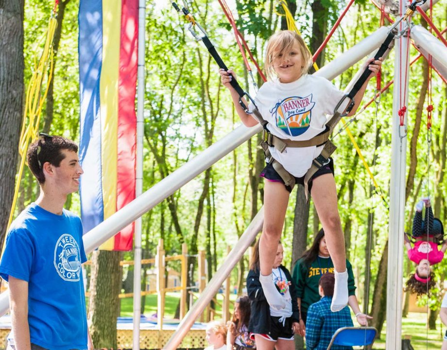 A counselor watches a young camper bungee