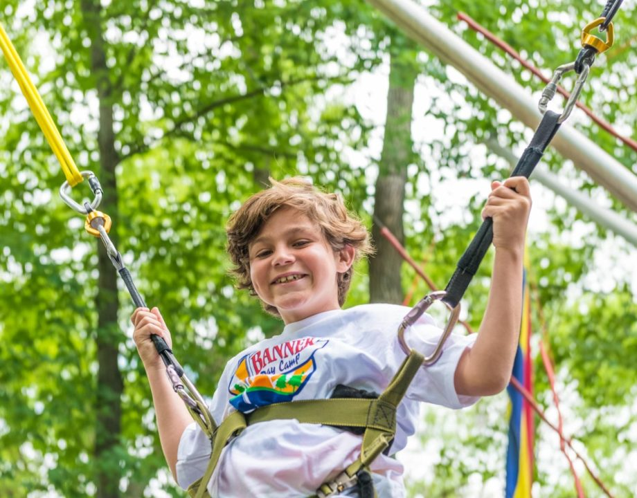 A young boy smiles while bungeeing