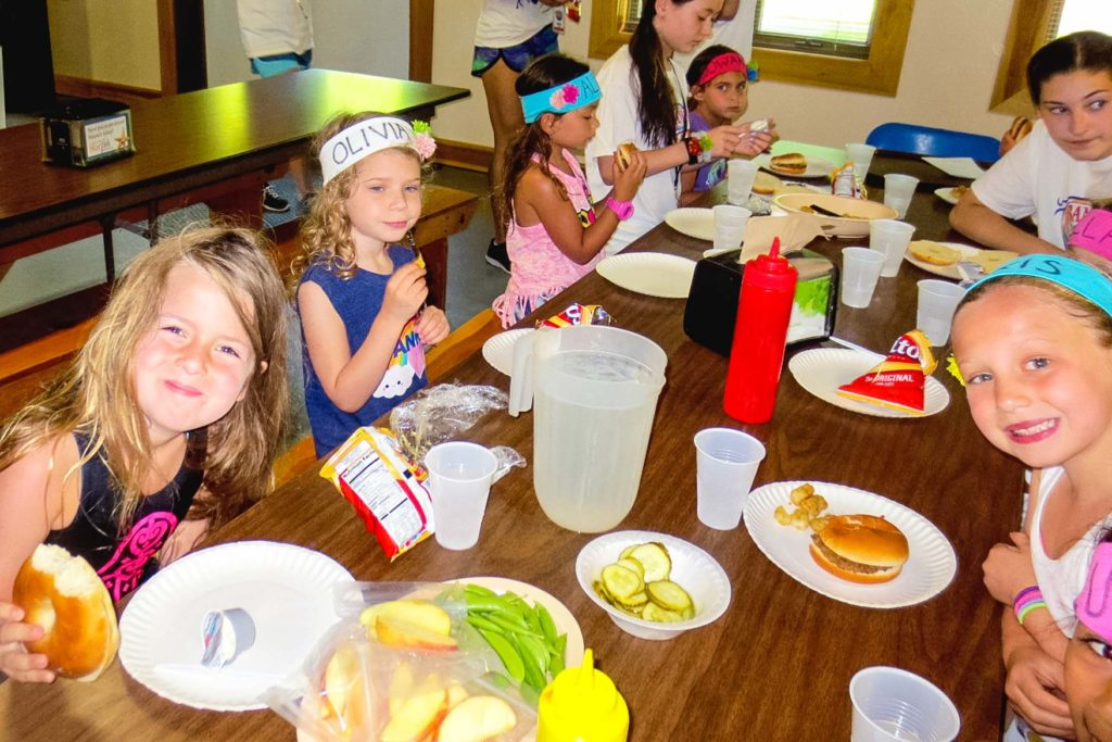 A group of young campers eating at a table