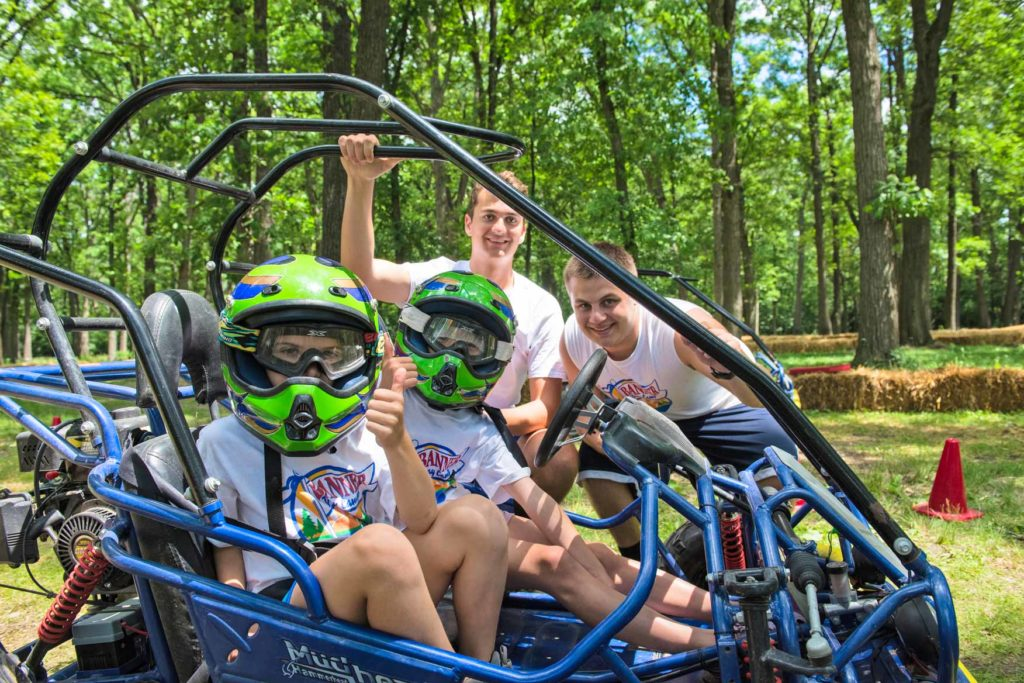 Two campers in a blue dune buggy with green helmets and two counselors outside the go kart.