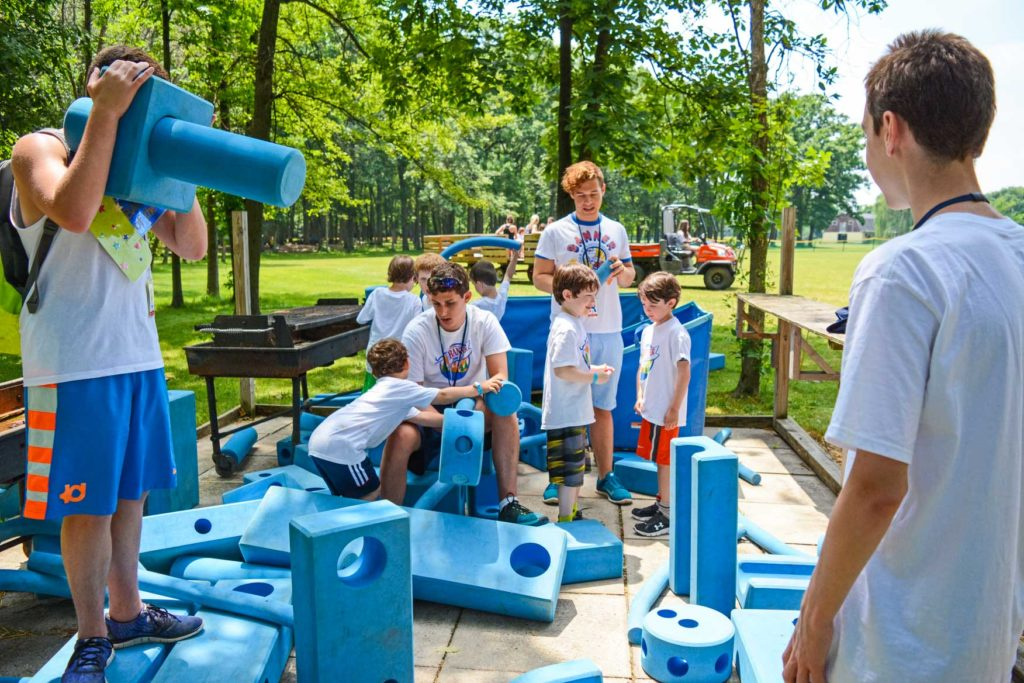 Campers playing with large blue blocks