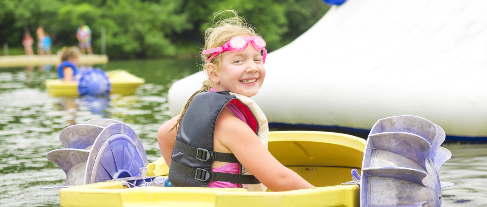 Girl camper in a peddle boat on the lake