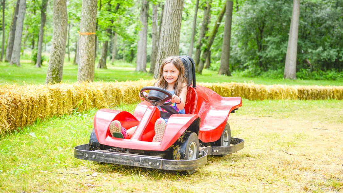 Girl camper driving a go-kart