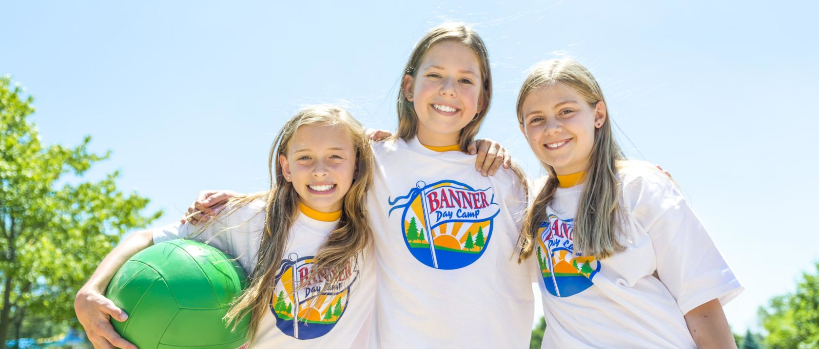 Three girl campers playing volleyball