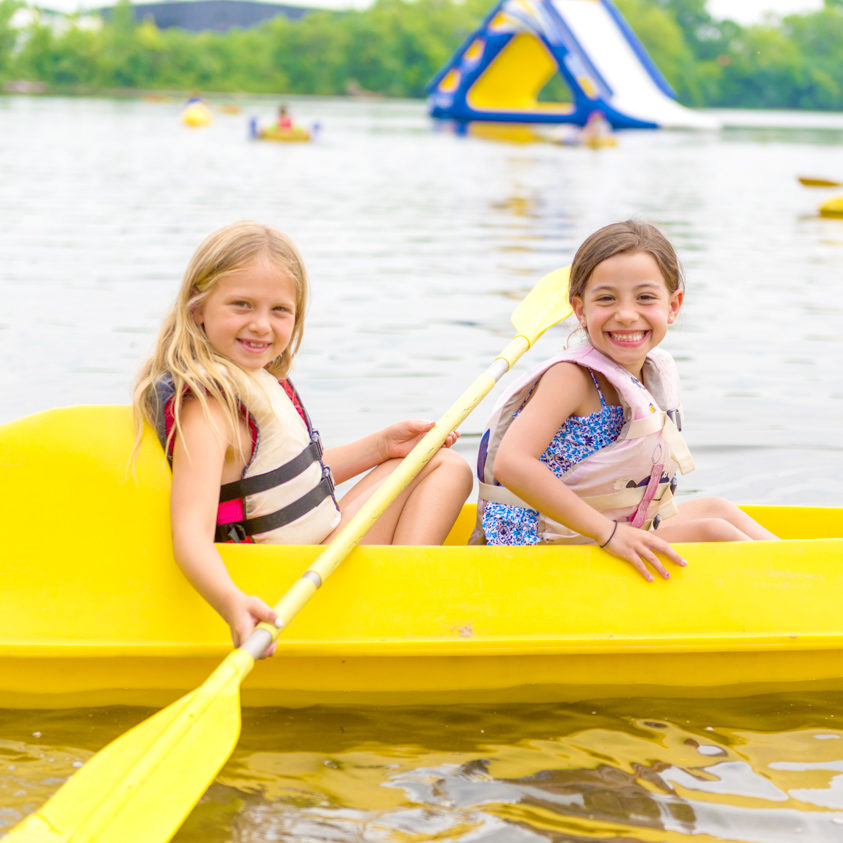 Two girl campers paddling in a kayak