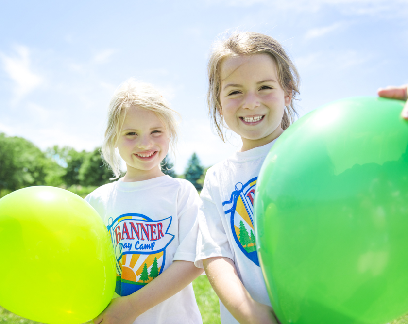 Two girl campers smiling holding balloons