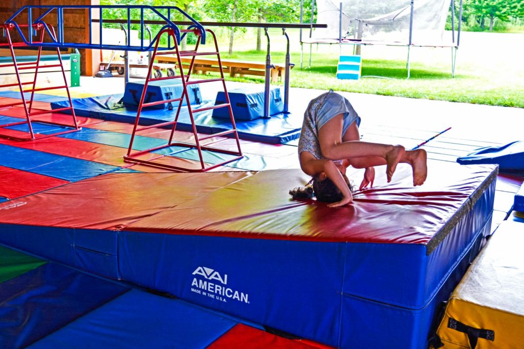 A child rolling down a mat