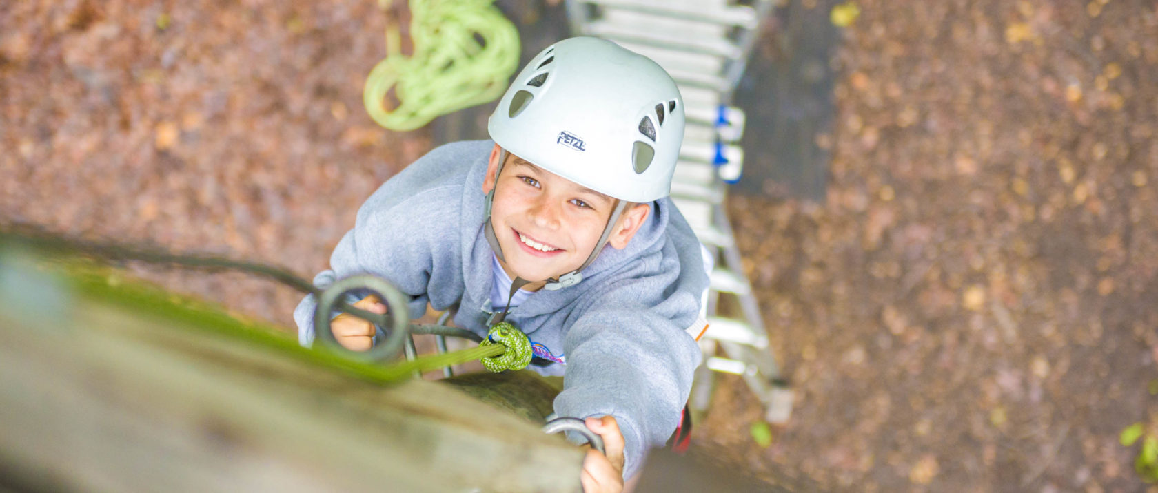 Boy camper climbing a pole on the ropes course