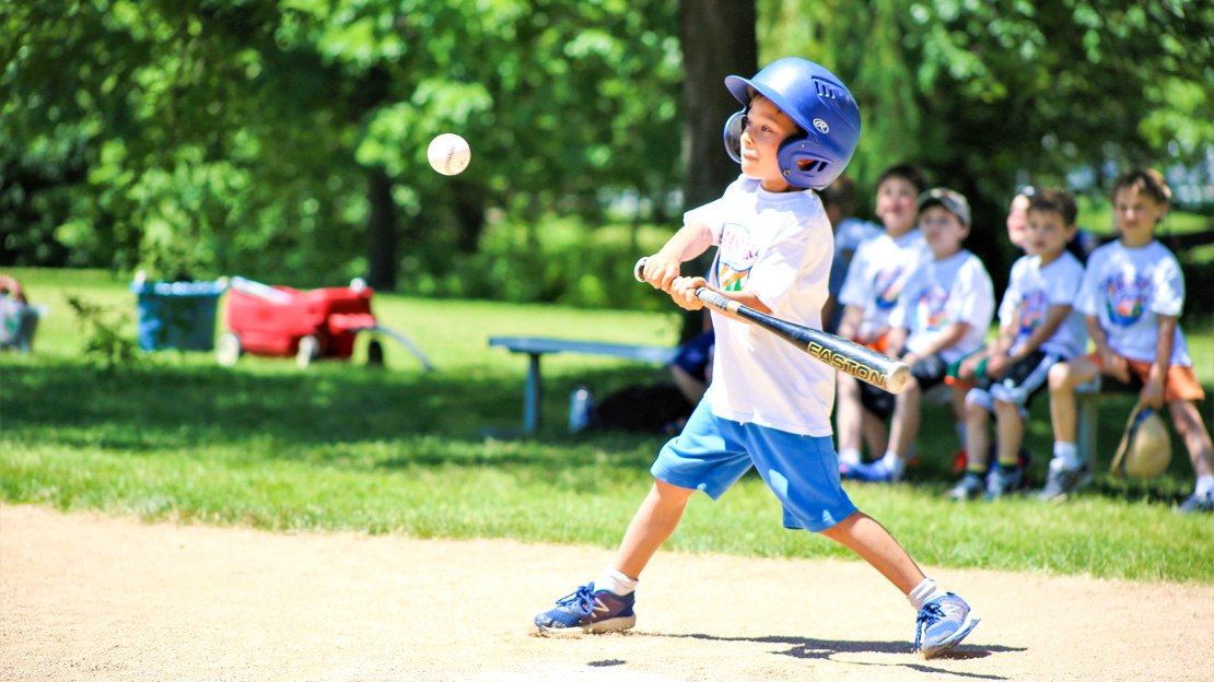 Camper hitting a baseball with a bat
