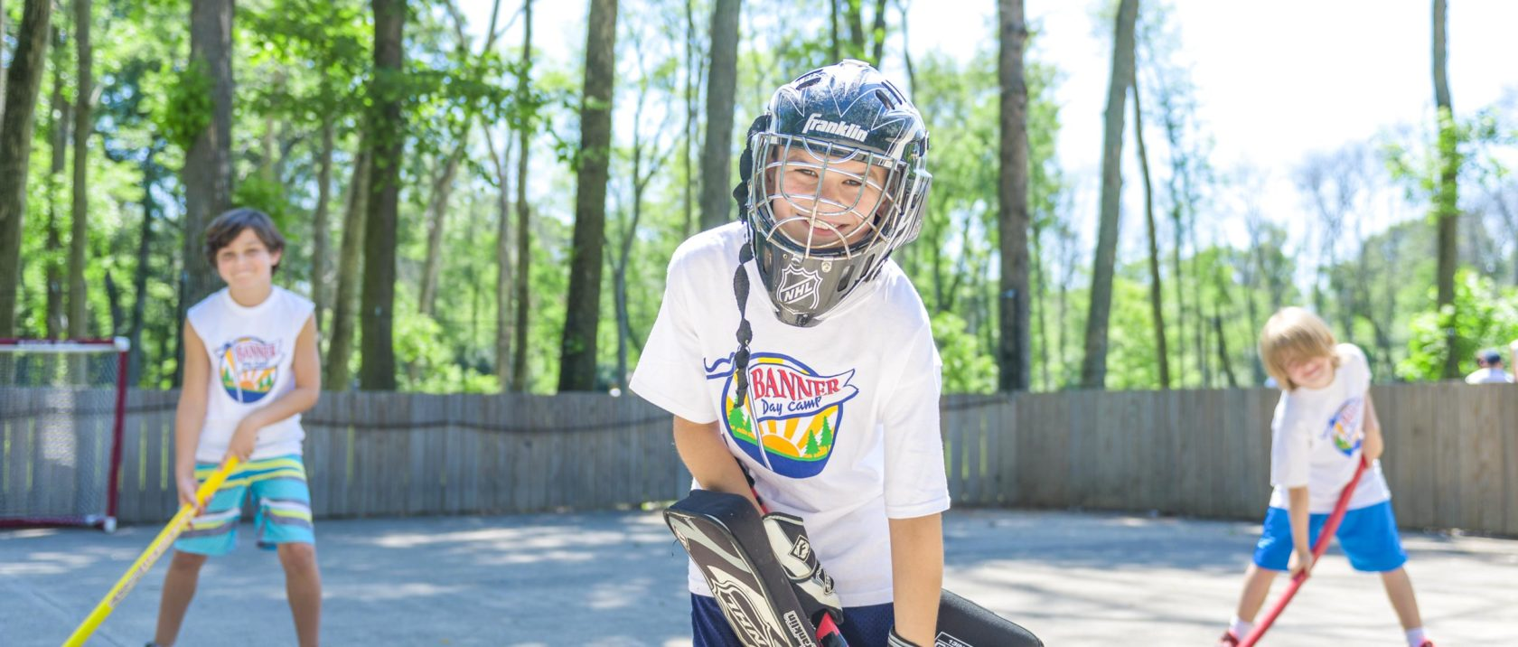 Boy campers playing street hockey