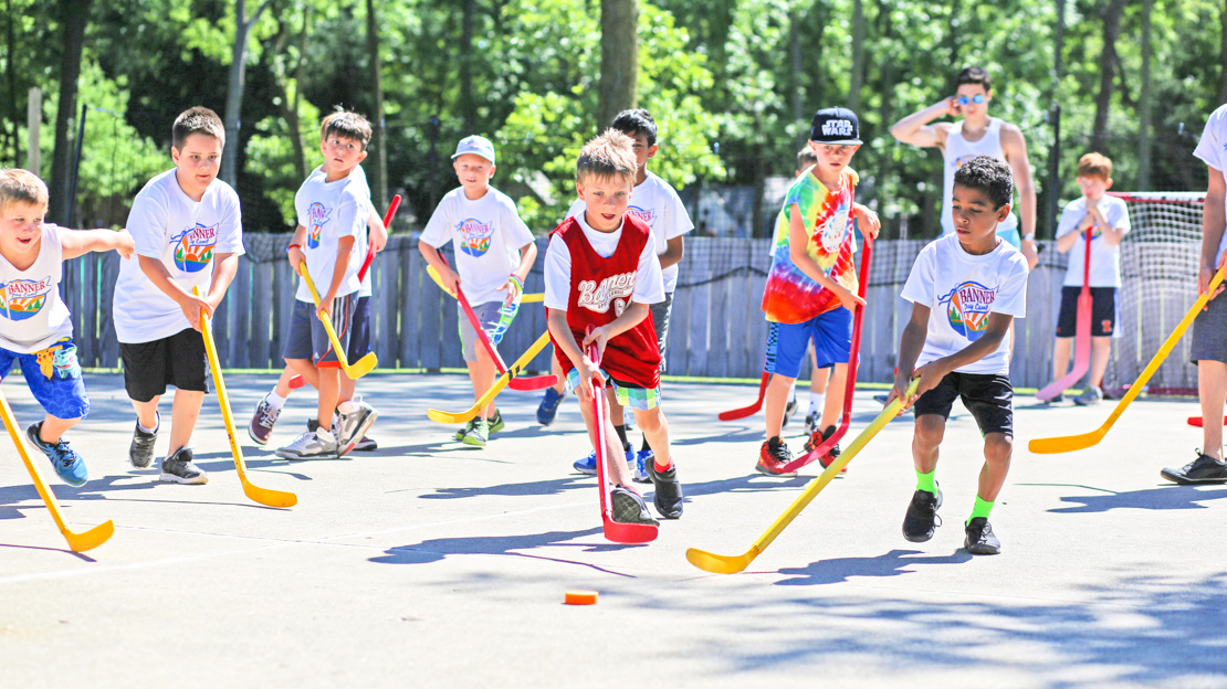 Campers playing street hockey