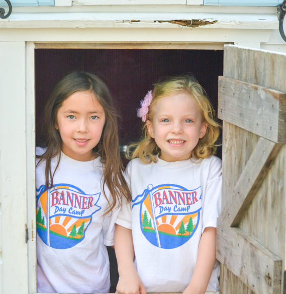 Two girl campers playing in a playhouse