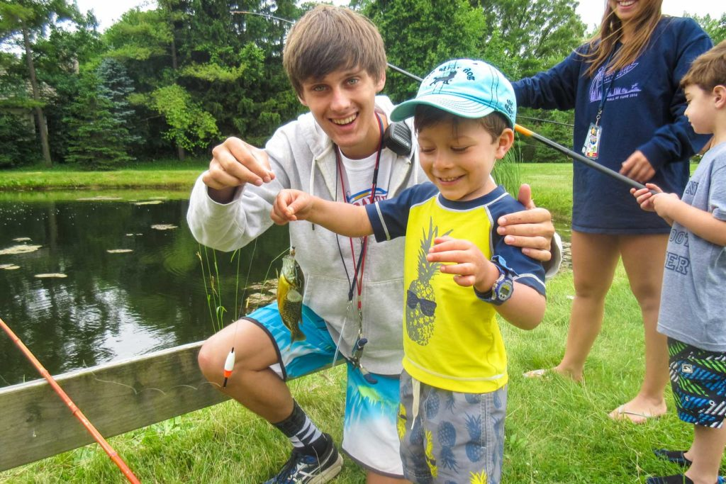 A camper and a counselor holding a fish they caught