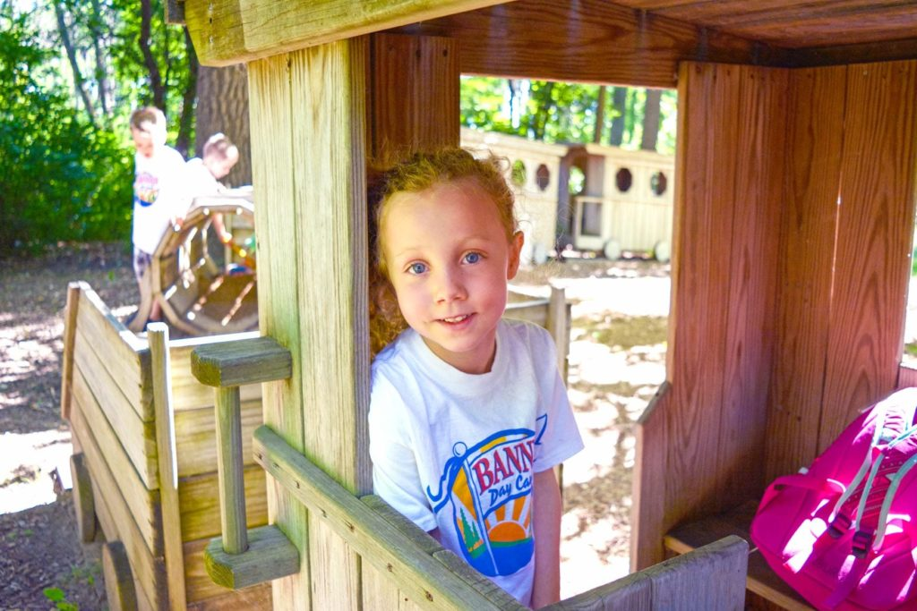 A child looking at the camera in a play train