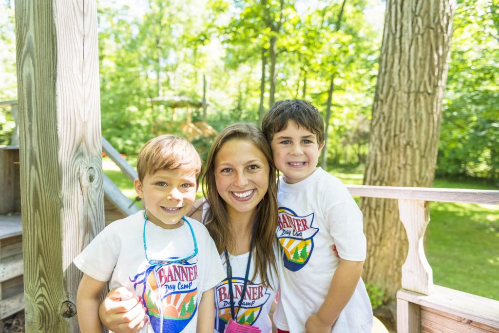 A counselor smiling with two little campers