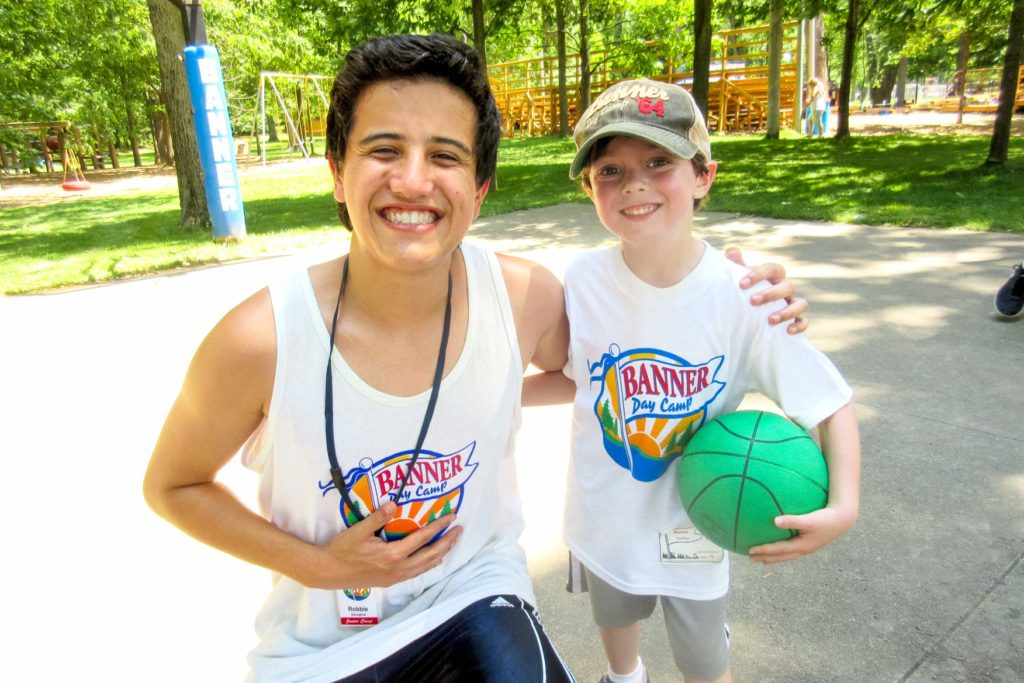 A camper and a counselor smiling with a basketball