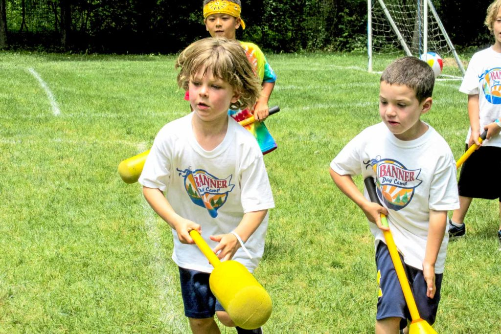 A group of young campers learning how to play lacrosse