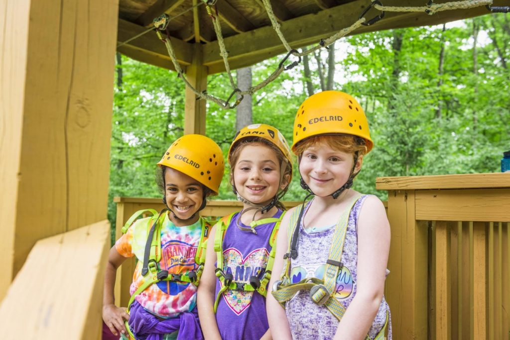 Three girls getting ready for the junior zipline smiling