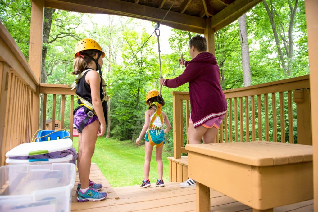 A girl getting ready to go on the junior zipline
