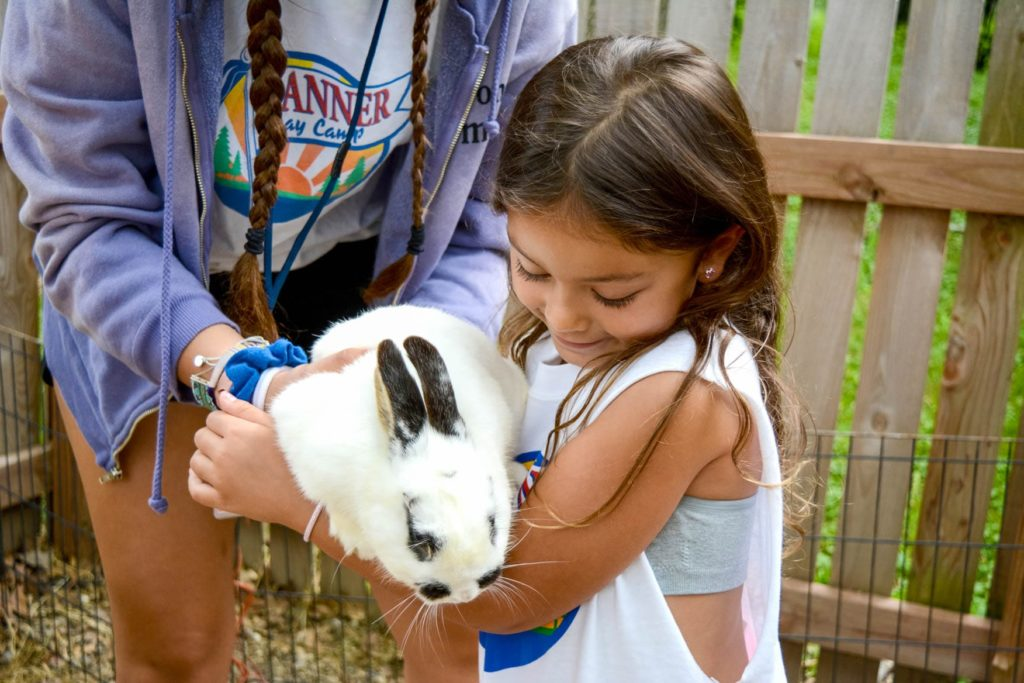 A young girl hugging a baby bunny