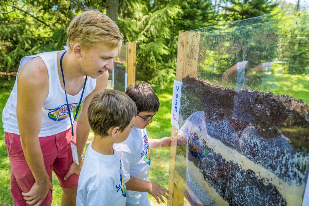A counselor showing two campers the ant farm at the farm