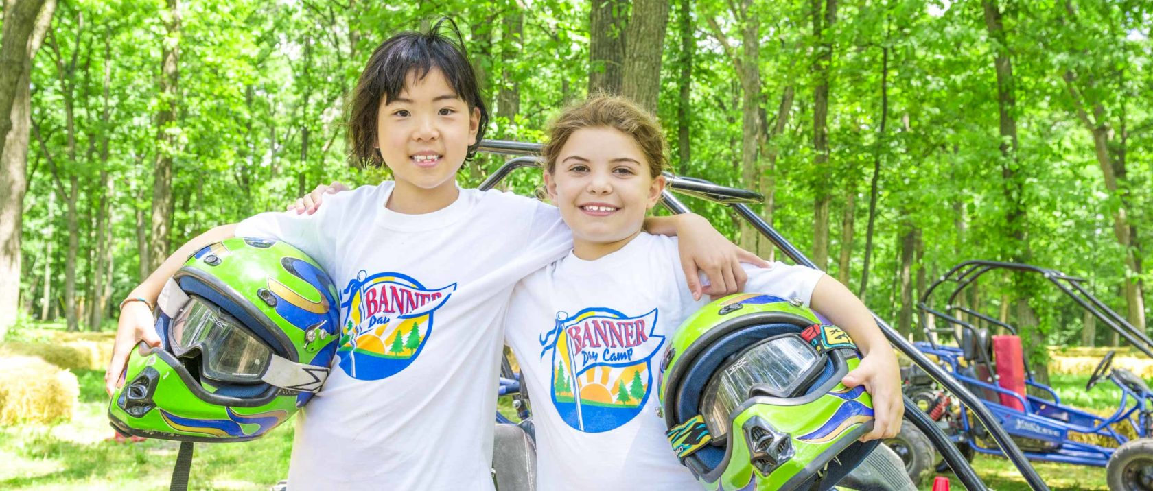 Two girl campers with go kart helmets in their hands smiling together